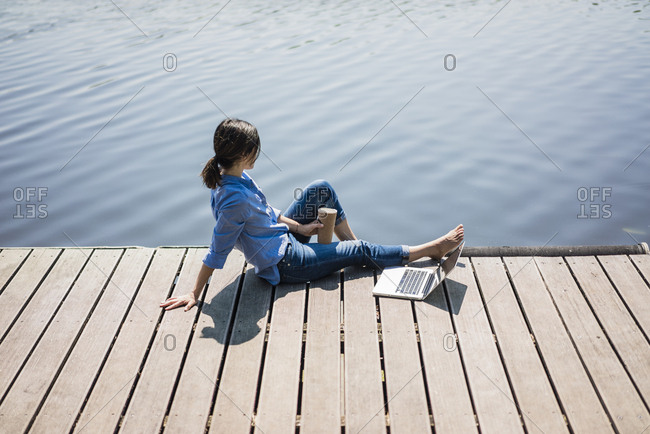 Mature woman sitting on a jetty at a lake- taking a break
