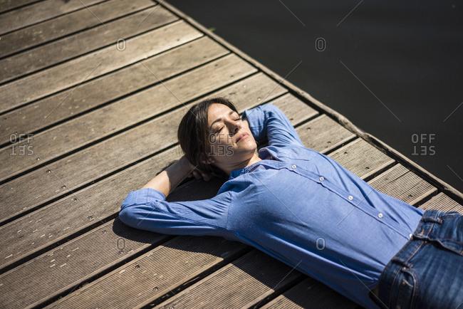 Mature woman taking a break- relaxing on a jetty