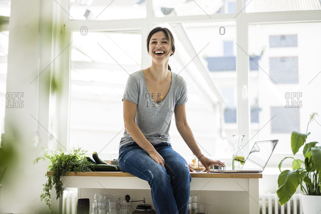 Woman sitting on kitchen table- searching for healthy recipes- using laptop