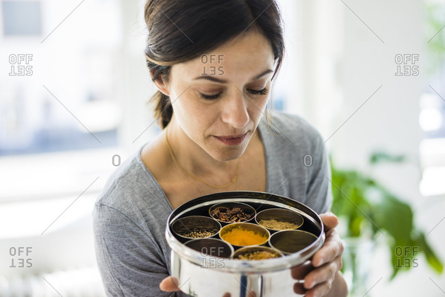 Woman holding tin box with choice of spices