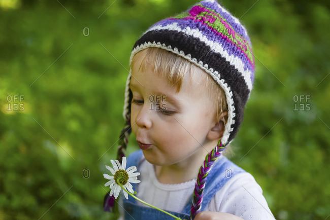 Portrait of little girl wearing knitted hat  blowing flower