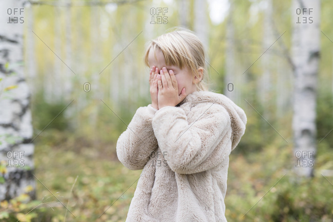 Blond girl playing Hide and Seek in a forest