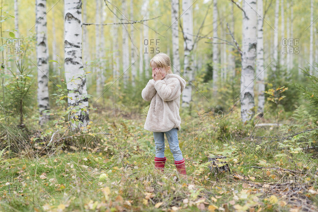 Blond girl playing Hide and Seek in a birch forest