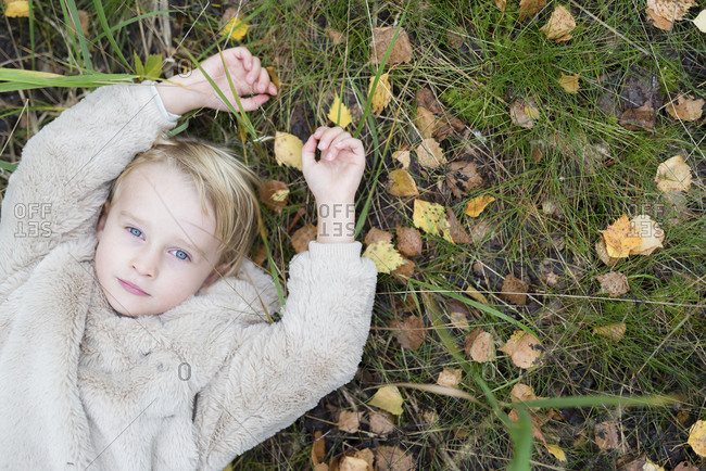Portrait of blond girl lying on a meadow in autumn- top view