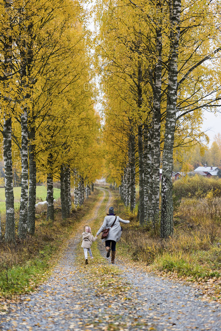 Finland- Kuopio- back view of mother and little daughter running side by side in autumn
