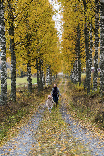 Finland- Kuopio- mother and little daughter strolling together in autumn