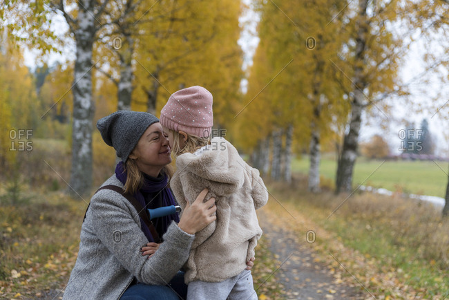 Mother and little daughter cuddling outdoors in autumn