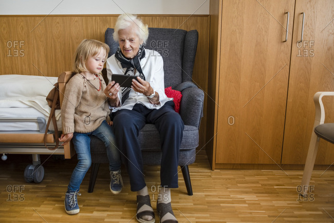 Aged woman watching together with her great-granddaughter photos on smartphone