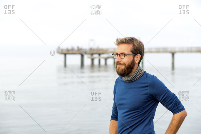 Germany- Rerik- bearded man in front of the sea looking at distance on hazy day