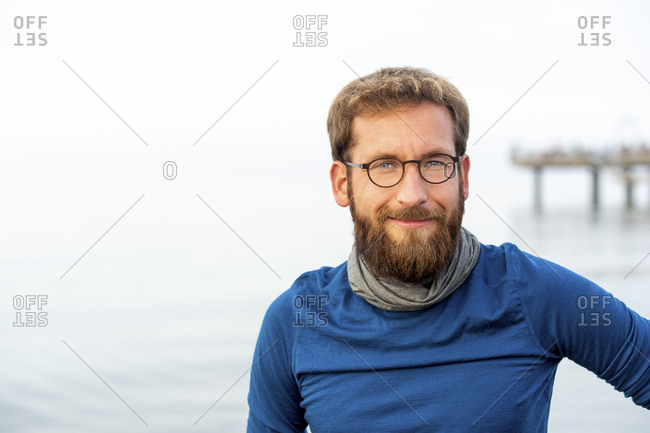 Germany- Rerik- portrait of bearded man in front of the sea wearing metal-rimmed spectacles