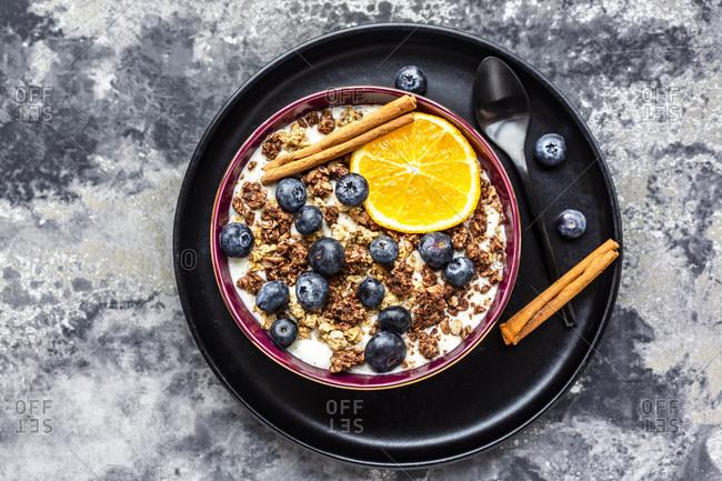 Crunchy muesli with blueberries- slice of orange and cinnamon sticks