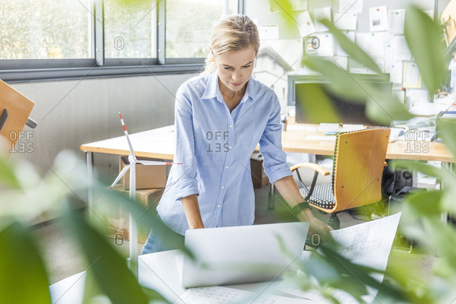 Woman in office with plan- laptop and wind turbine model on table