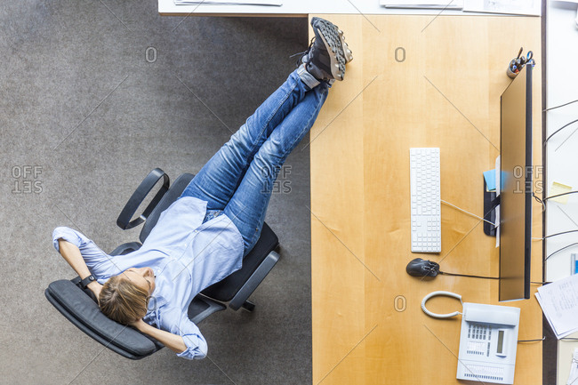 Top view of woman relaxing in chair at desk in office