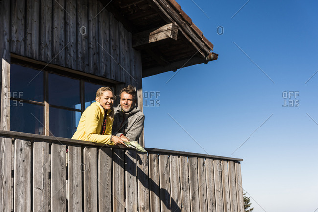 Couple leaning on balcony of a mountain hut- holding map