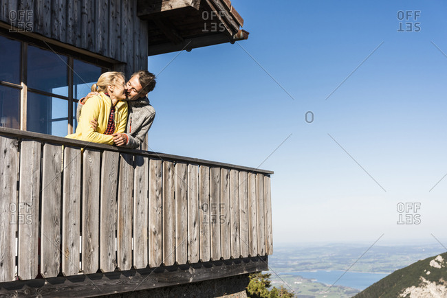 Couple leaning on balcony of a mountain hut- kissing
