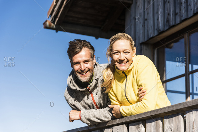 Couple leaning on balcony of a mountain hut- smiling