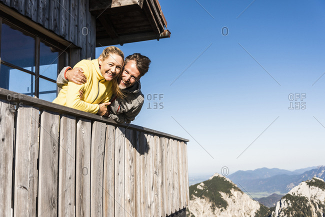 Couple leaning on balcony of a mountain hut- with arms around