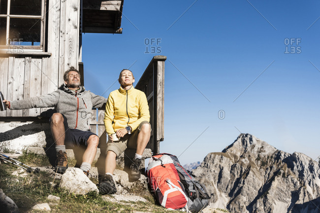 Hiking couple sitting in front of mountain hut- taking a break