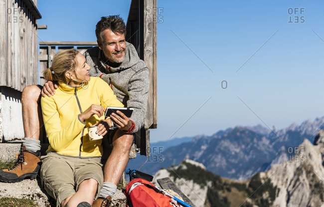 Hiking couple sitting in front of mountain hut- taking a break- looking at smartphone