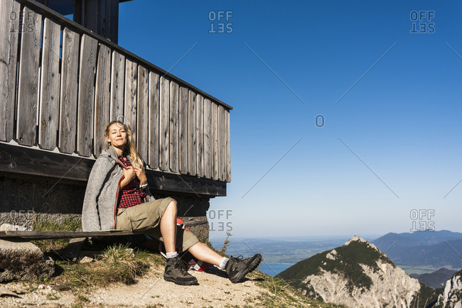 Woman relaxing at a mountain hut- enjoying the sun