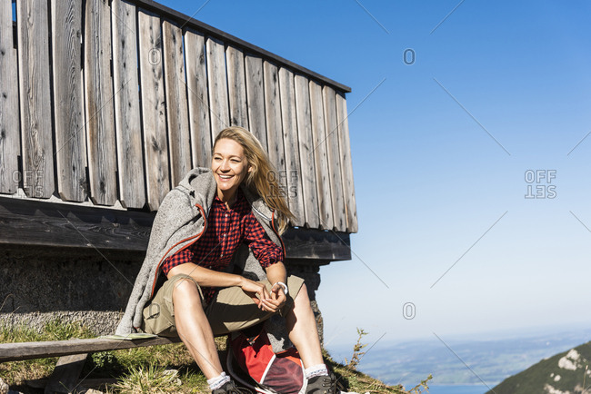 Laughing woman taking a break at a mountain hut