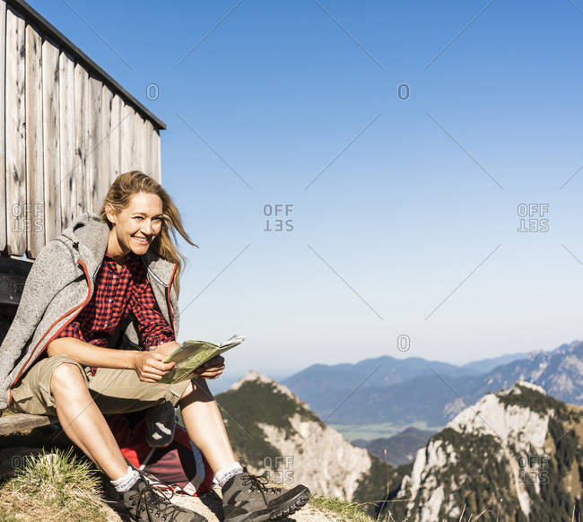 Laughing woman taking a break at a mountain hut- holding map