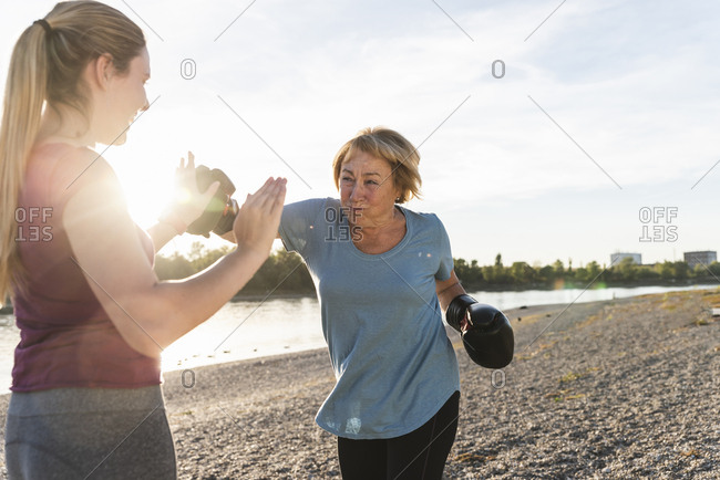 Grandmother doing boxing training with her graddaughter at the river