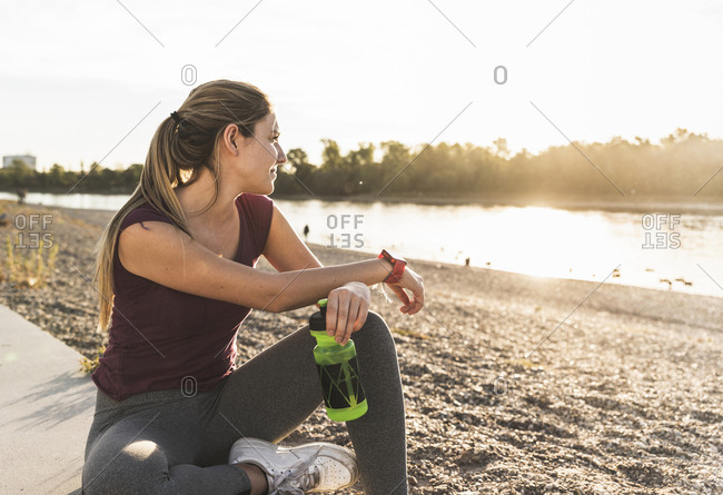 Young woman taking a break after exercising at the river