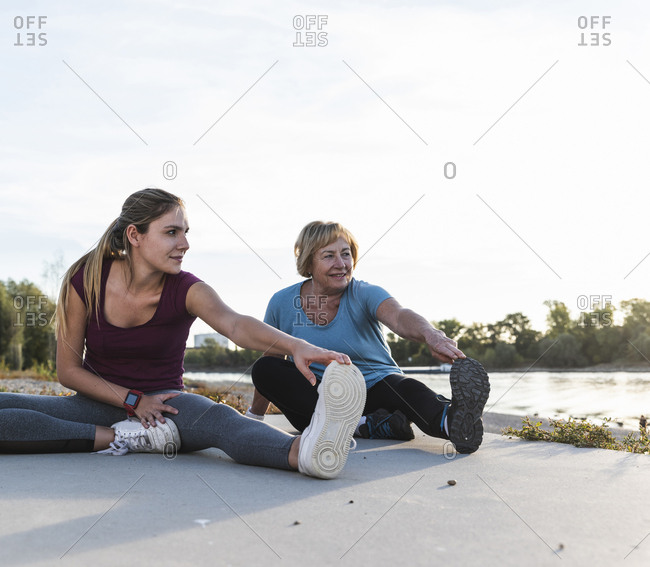 Grandmother and granddaughter sitting on ground at the river- warming up for training