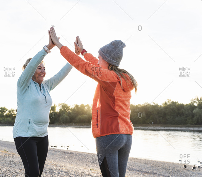 Grandmother and granddaughter high-fiving after training at the river