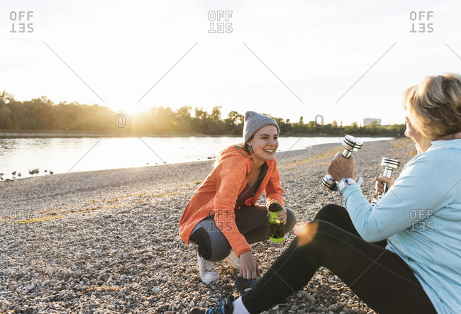 Grandmother and granddaughter taking a break at the river after dumbbell training