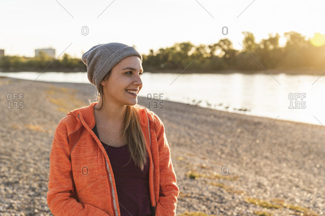 Portrait of a sportive young woman at the river- weraing a beanie hat