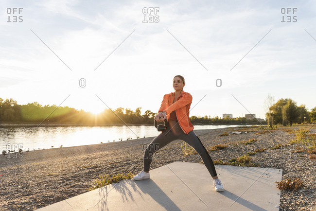 Young woman exercising with a kettlebell at the river