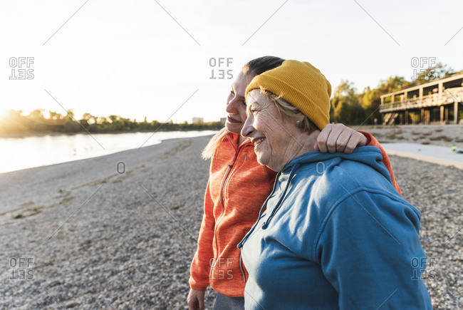 Fit grandmother and granddaughter walking at the river with arms around- having fun