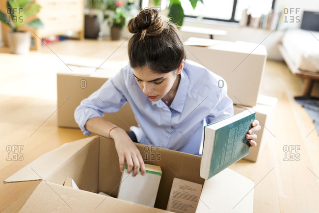 Young woman unpacking cardboard box in new apartment