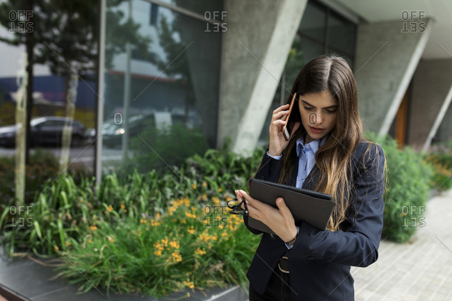 Young businesswoman using tablet and cell phone in the city