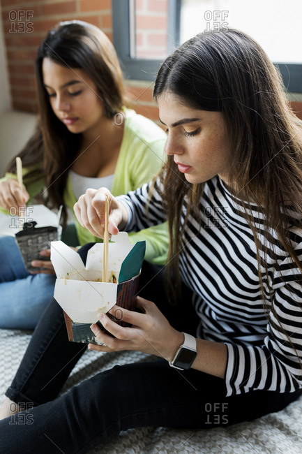 Two young women having Asian takeaway food at home
