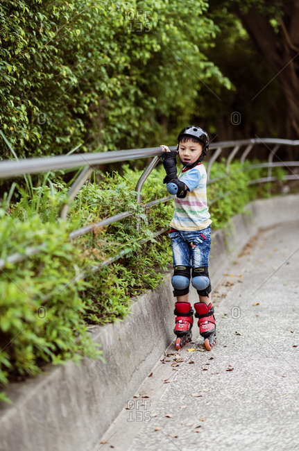 Child holding the railing to learning rollerblading in the park