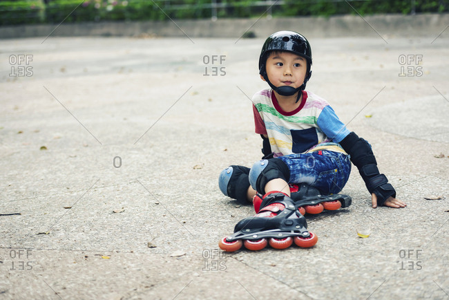 Kid fall down when he playing line skates in the park