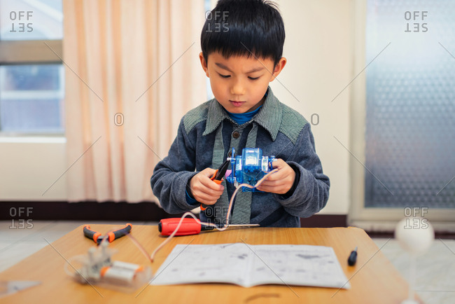 Little boy concentrate his attention on assembling robot carefully.