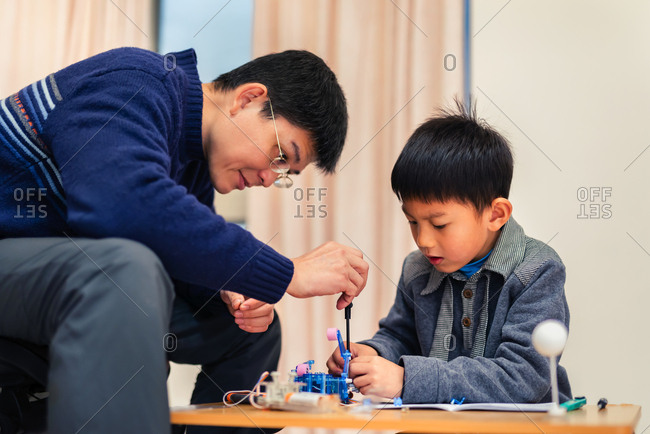 Father and child concentrate their attention on  assembling robot carefully