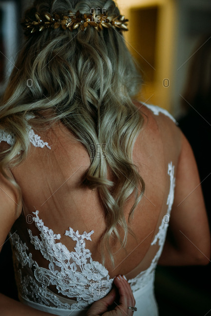 Detail of a bride zipping up the back of her dress