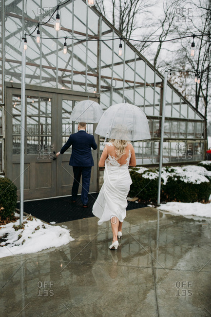 Bride and groom walking in the rain under umbrellas
