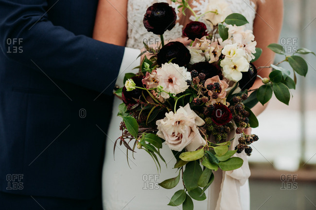 Bride and groom holding beautiful flower bouquet