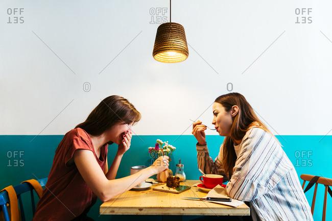 Smiling girlfriends having breakfast in a coffee shop.