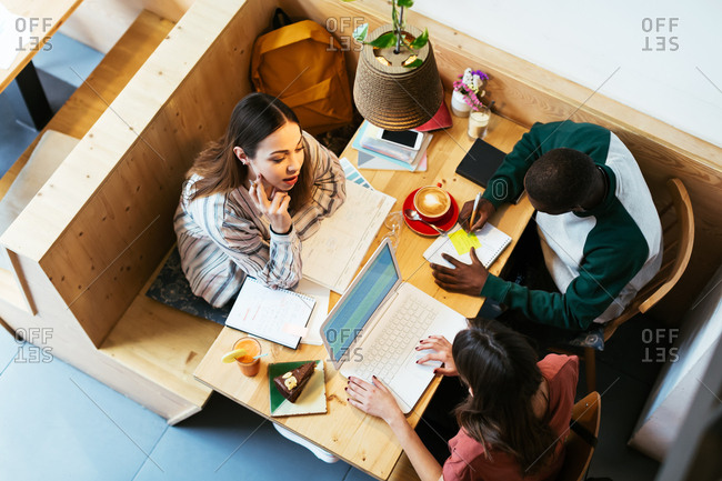 Students working together sitting on table in a coffee shop from above.