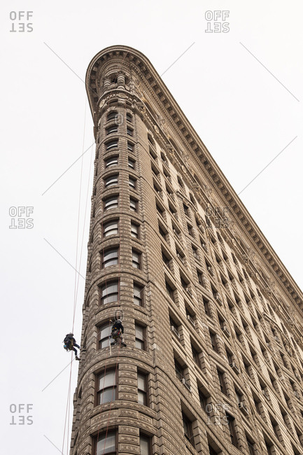Window washer scaling the side of the famous Flatiron building in New York City, New York