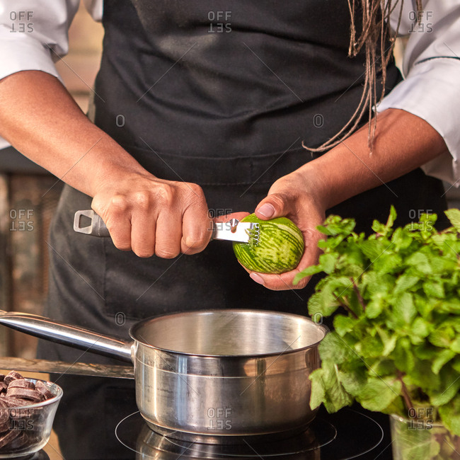 Professional confectioner cuts fresh lime peel into pan for cooking homemade dessert on a hob at the kitchen table. Step by step dessert making process.