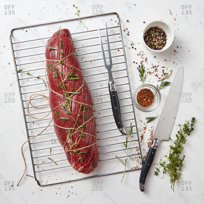Fresh raw meat, whole piece of fillet with herbs and spices on a stone white background. Cooking ingredients for healthy organic meals. Top view.