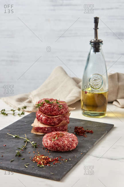 Fresh ground raw beef meat with herb thyme, paprika for homemade bbq on a black shale plate on a white background with textile towel, place for text.